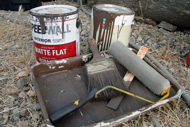 Cans of brown paint with a brush and roller.